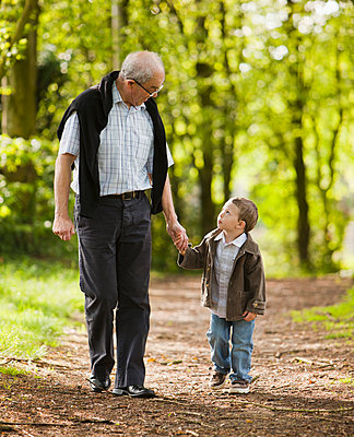 Caucasian grandfather and grandson walking in woods - p555m1479389 by Mike Kemp