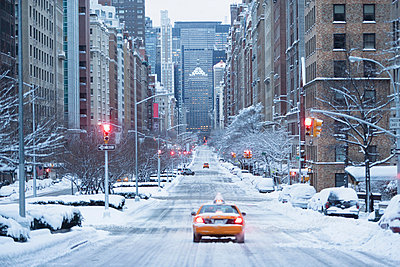Taxi on snowy city street - p924m807183f by Ditto
