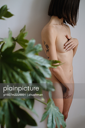 Portrait of a hiding nude woman with a plant - p1607m2228891 by zhushman