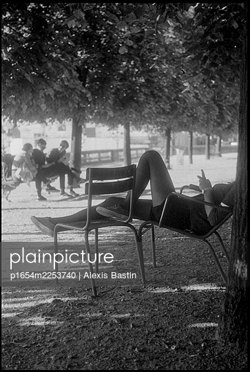 Youg Girl sitting on a chair in a park in Paris - p1654m2253740 by Alexis Bastin