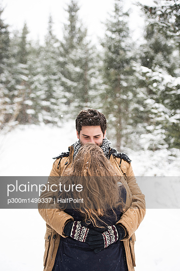 Happy young couple hugging each other in winter landscape