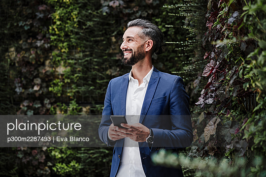 Male entrepreneur with mobile phone smiling while standing by plants - p300m2287493 by Eva Blanco