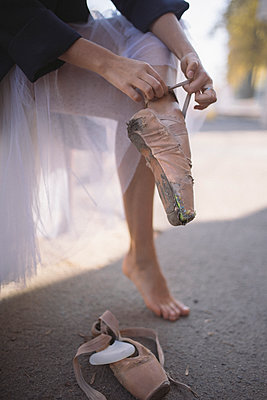 Low section of ballerina wearing torn ballet shoes on road in city - p1166m2039987 by Cavan Images