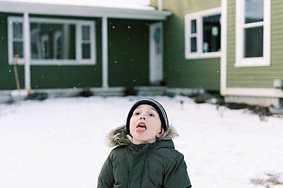Little boy standing in his front yard trying to catch snow flakes. - p1166m2152174 by Cavan Images