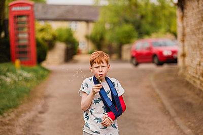 Boy with a broken arm blowing dandelion seeds - p300m1450160 by Nicole Matthews