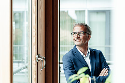 Smiling male business professional looking through window in office - p300m2265751 by Gustafsson