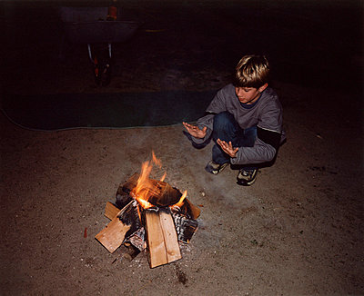 A boy next to a campfire - p3012781f by fStop