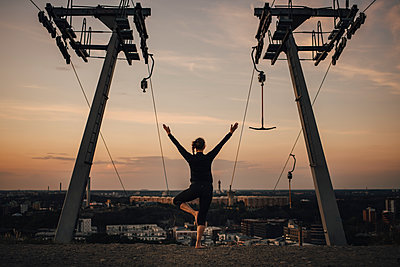 Mature female athlete practicing yoga against sky during sunset - p426m2270846 by Maskot
