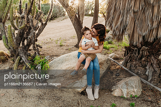 Mother embracing and kissing young son on rock in sunny cactus garden - p1166m2136687 by Cavan Images