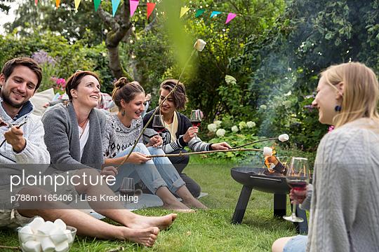 Freunde auf einer Gartenparty rösten Marshmallows  - p788m1165406 von Lisa Krechting