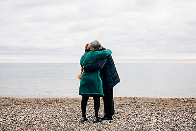 Rear view of senior couple hugging next to the beach - p1166m2078393 by Cavan Images