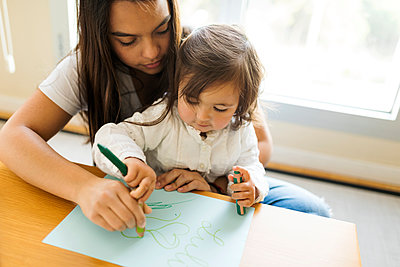 Nanny helping a toddler with a drawing with colored pencils - p1166m2085010 by Cavan Images