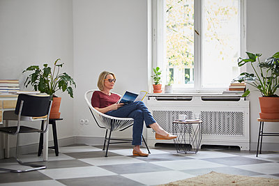 Mature woman reading magazine at home - p300m2030353 by Rainer Berg