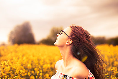 Smiling young woman in a rape field - p300m2276579 by Sebastian Dorn