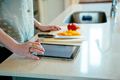 Woman using digital tablet and chopping food in domestic kitchen - p555m1444099 by Inti St Clair