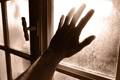 Woman's hand on windowpane - p945m2182290 by aurelia frey