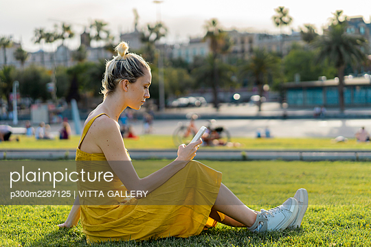 Woman text messaging through mobile phone while sitting on grass - p300m2287125 by VITTA GALLERY