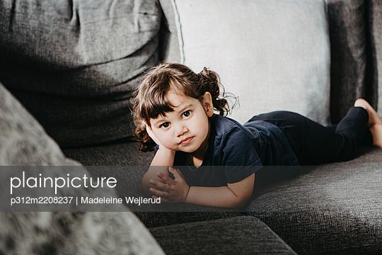 Girl lying on sofa - p312m2208237 by Madeleine Wejlerud