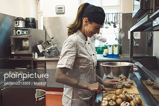 Side view of smiling female chef cutting mushrooms at kitchen counter - p426m2213303 by Maskot
