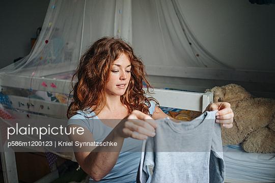 Rothaarige Frau faltet Kleidungsstück zusammen  - p586m1200123 von Kniel Synnatzschke