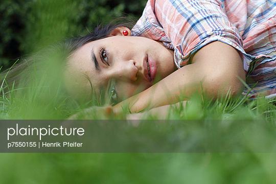 Girl lying in a park - p7550155 by Henrik Pfeifer