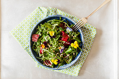 Bowl with salad, lamb's lettuce, rucola, radicchio and edible flowers - p300m1567945 by Eva Gruendemann