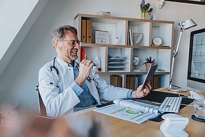 Mature doctor talking on video call over digital tablet while sitting at doctor's office - p300m2266903 by Mareen Fischinger