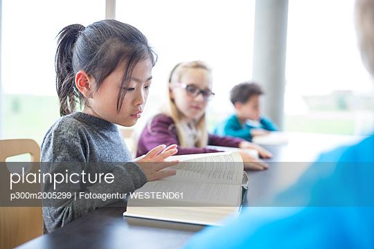 Schoolgirl reading book on table in school break room - p300m2005299 von Fotoagentur WESTEND61