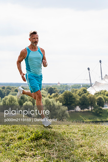Sporty man jogging in a park - p300m2119169 by Daniel Ingold