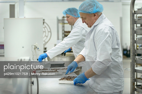 Bakers prepare trays of product in cake factory - p429m1021753f by Monty Rakusen