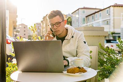 Man talking through mobile phone while using laptop on table at sidewalk cafe - p1166m2060532 by Cavan Social