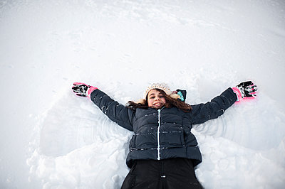 Girl smiling while making snow angel in the snow in front yard - p1166m2136735 by Cavan Images