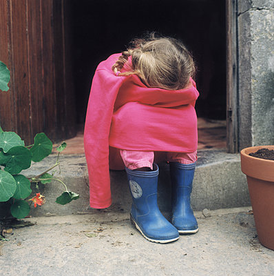 Little girl sitting at front door - p1270m1105836 by Annabel Sougne