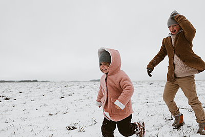 Brother and little sister playing together on snow-covered meadow - p300m2058996 by Katharina Mikhrin