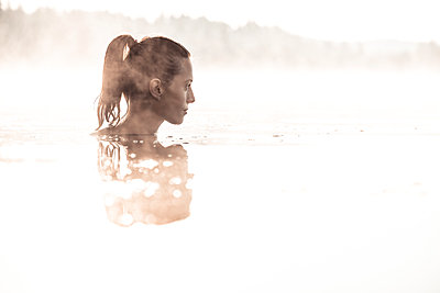 Woman bathing in a lake at morning mist - p300m2156882 by Wilfried Feder