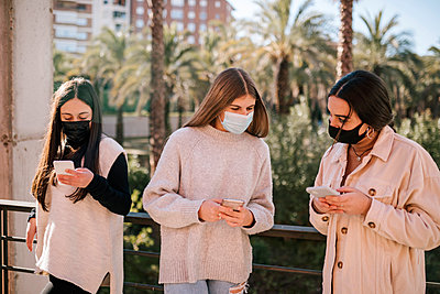 Teenage friends wearing face masks using mobile phones while standing in park - p300m2251626 by LUPE RODRIGUEZ