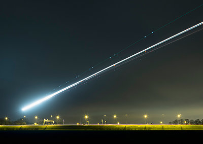 Night shot of airplane approaching Schiphol airport - p429m895965 by Mischa Keijser