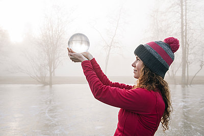 Woman holding up crystal ball on frozen lake - p924m1230076 by Pete Saloutos