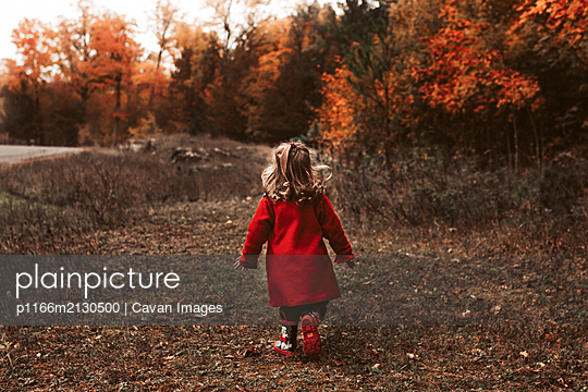 Child walking outside wearing red coat on a beautiful fall day - p1166m2130500 by Cavan Images