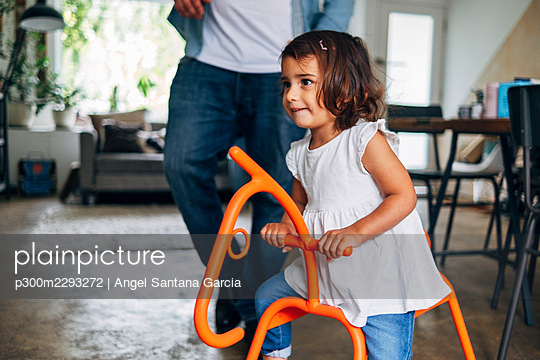 Cute girl playing on rocking horse while father in background at home - p300m2293272 by Angel Santana Garcia
