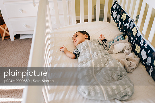 Baby boy lying awake in crib, high angle view - p924m2090639 by Sara Monika