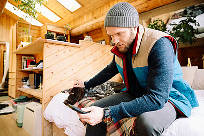 Man with dog using smart phone in cabin - p1192m2093916 by Hero Images