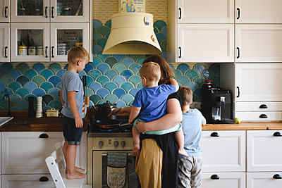 Mother cooking with her three sons in the kitchen - p300m2119652 von Ekaterina Yakunina