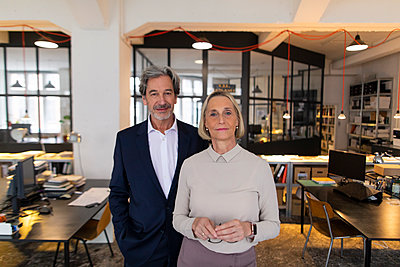Portait of confident businessman and businesswoman in office - p300m2156017 by Gustafsson
