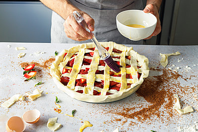 Hands of man applying egg wash to raw strawberry pie - p300m2265806 by Ignacio Ferrándiz Roig