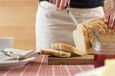 Woman cutting home-made yeast bread on chopping board, partial view - p300m941038f by Sandra Bielmeier