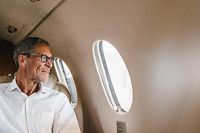 Mature businessman in private jet - p586m1208485 by Kniel Synnatzschke