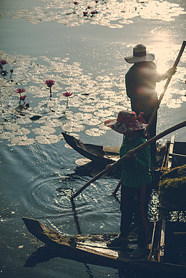 Two fishermen at sunrise in Angkor Wat - p795m2223232 by JanJasperKlein