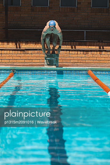 Young Caucasian male swimmer ready to jump into water of a swimming pool - p1315m2091016 by Wavebreak
