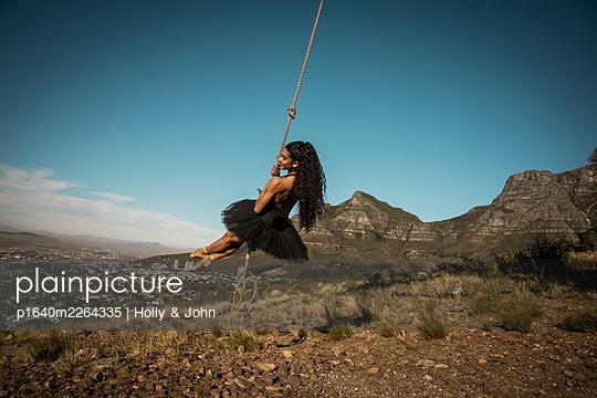 Brünette Frau schaukelt vor blauem Himmel - p1640m2264335 von Holly & John